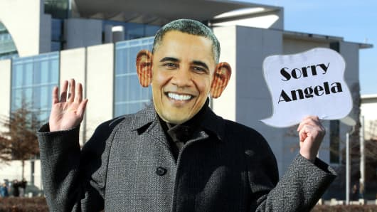 "An activist of the ""Office for unusual measures"" dressed as President Obama holds a sign reading ""Sorry Angela"" in front of the Chancellery in Berlin on Oct. 31, 2013."