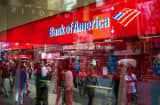 The reflections of pedestrians walking are seen in the window of a Bank of America branch in New York.