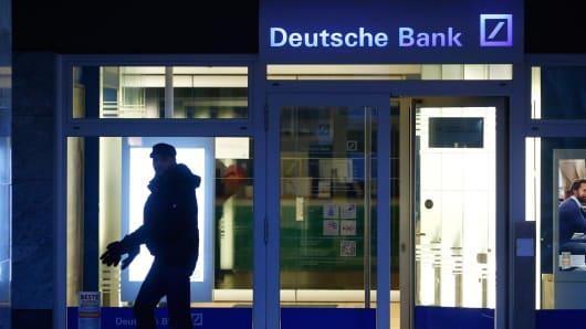 A pedestrian passes a Deutsche Bank branch in Frankfurt, Germany.