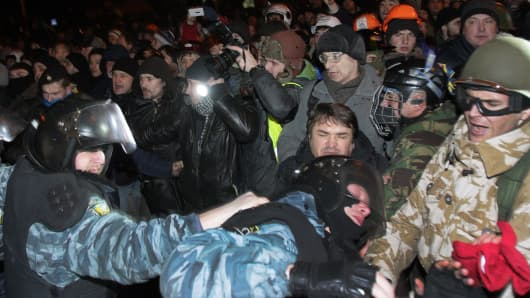Ukrainian pro-European opposition activists clash with riot police after the protesting rally near a district court in Kiev on January 11, 2014.