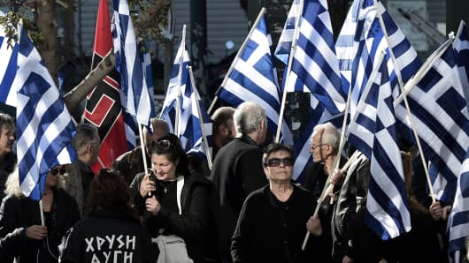 Supporters of ultra-nationalist party Golden Dawn shout slogans outside a courthouse in Athens on January 11, 2014.
