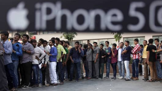 Indians stands in a queue to purchase the new iPhone 5c and 5s during its launch in Ahmadabad, India.