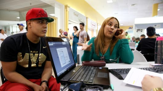 Carlos Salvador sits with his mother, Yadelmis Ramirez, as she speaks with an insurance agent as they purchase Obamacare coverage in Miami.