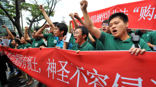 Chinese students shout slogans with a red banner reading 'Diaoyu island is Chinese territory, we will not allow invasion to the territory' during an anti-Japanese rally near the Japanese embassy in Seoul on September 20, 2012.