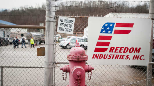 Workers walk behind the fence at the Freedom Industries building in Charleston, West Virginia on Saturday, January 11, 2014.