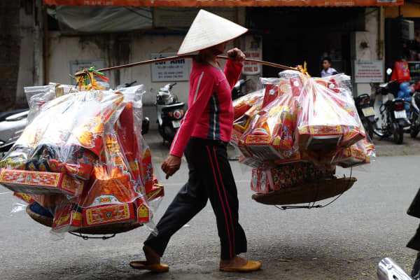 A vendor hawks votive paper along a street in downtown Hanoi on January 8, 2014.