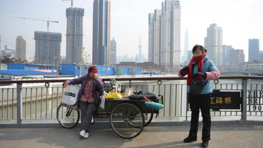 Two women sell goods on a bridge in Shanghai.