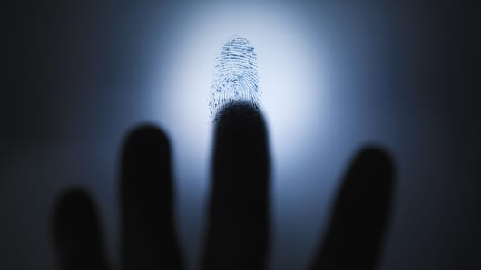 Blurred hand hovering over fingerprint.