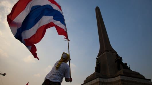 Anti-government protester waves a Thailand flag over the crowd in front of Victory Monument.