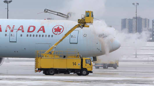 Air Canada planes get de-iced on the tarmac by crews at Pearson International Airport in Toronto, January 20, 2014.