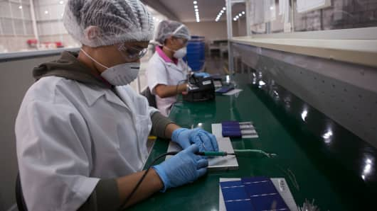 Employees assemble photovoltaic panels at a Solartec SA renewable energy assembly plant in Irapuato, Mexico, on Thursday, Nov. 28, 2013.