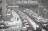 Traffic moves slowly through the snow into the Holland Tunnel from Manhattan during a snowstorm on January 21, 2014 in New York City.