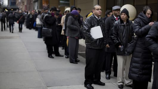 Job seekers wait in line to enter a job fair in New York.