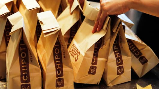 An employee carries bags of tortilla chips at a Chipotle Mexican Grill Inc. restaurant in Hollywood, California, July 16, 2013.