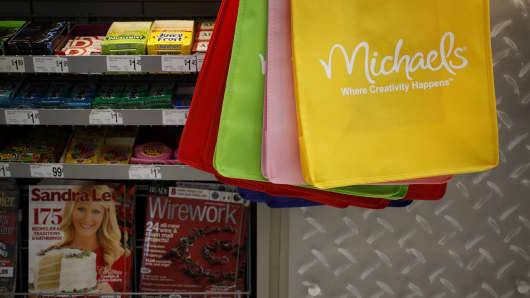 Reusable shopping bags are displayed beneath a checkout counter at a Michaels craft store in Cincinnati, Ohio.