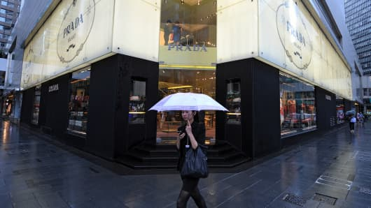 A woman walks past luxury retailer Prada in Hong Kong.