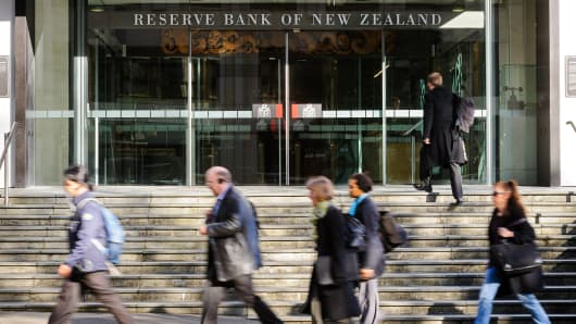 Pedestrians walk past the Reserve Bank of New Zealand headquarters in Wellington, New Zealand, on Thursday, Sept. 13, 2012.