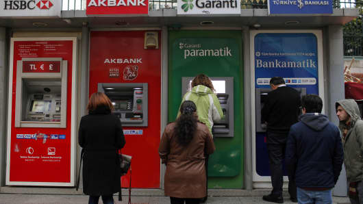 Customers queue outside automated teller machines in Istanbul, Turkey on Monday.