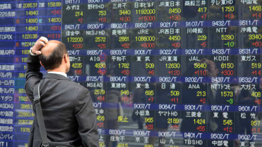 A pedestrain looks at a share prices board in Tokyo