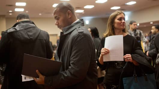 Job seekers wait to talk to recruiters and fill out applications at a job fair in New York.