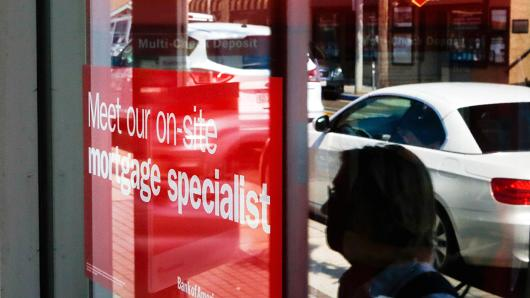 The reflection of pedestrians walking is seen in a window next to a sign advertising home mortgage services at a Bank of America Corp. branch in Manhattan Beach, California.