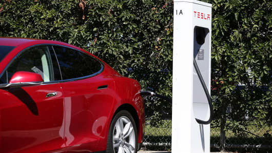 A Tesla Model S sedan is seen plugged into a new Tesla Supercharger.