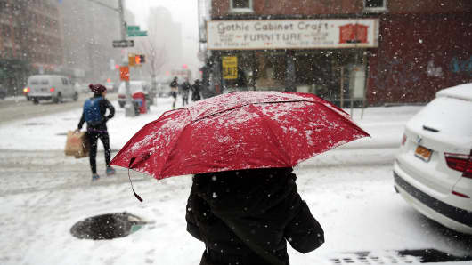 People walk in Manhattan during a snowstorm on January 21, 2014 in New York City.