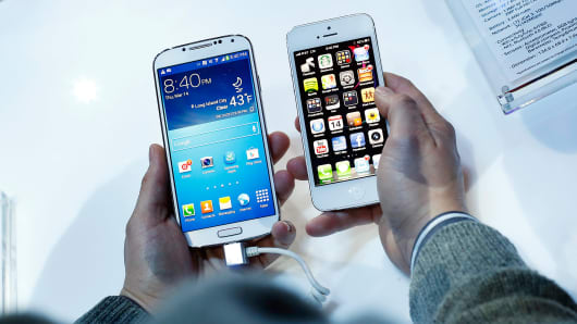 A man holds a Samsung Electronics Co. Galaxy S4 smartphone, left, next to an Apple Inc. iPhone 5.