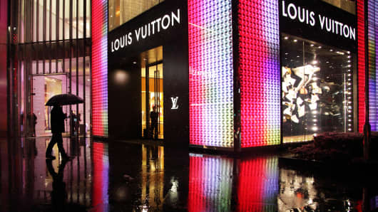 A man holding an umbrella walks past a Louis Vuitton store in Shanghai.