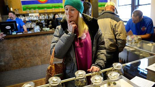 Kristin Brinckerhoff ponders the selection of marijuana at 3D Cannabis Center in Denver, Jan. 2, 2014.