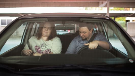 Ben and Erika Trowell leave home for work in the car they share in Phoenix.