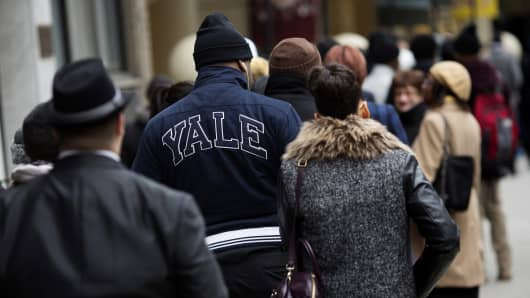 A job seekers wears a Yale jacket while waiting in line to enter a job fair in New York.