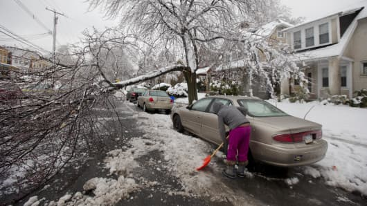 A Philadelphia resident clears snow near a downed tree limb Wednesday