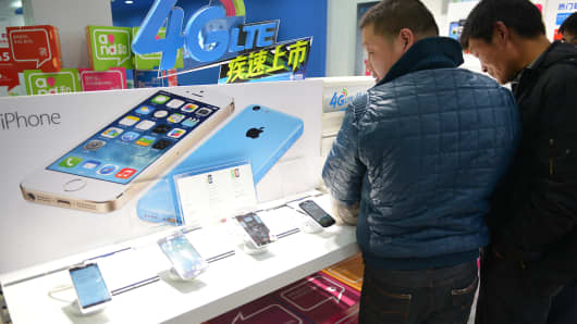 Customers looking at Apple iPhones in a China Mobile store in Shanghai.