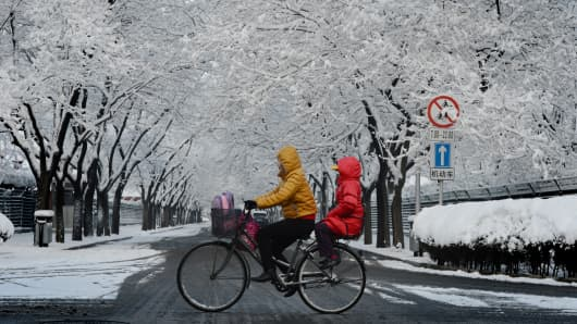 A cyclist rides a bicyle after snowfall on a road in Beijing.