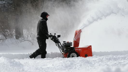 A man in Boxford, Mass. uses a snowblower to clear snow from his front driveway after a nor'easter covered New England, January 3, 2014.