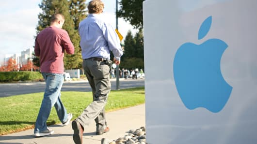 Apple employees walk towards the Apple Headquarters in Cupertino, California.