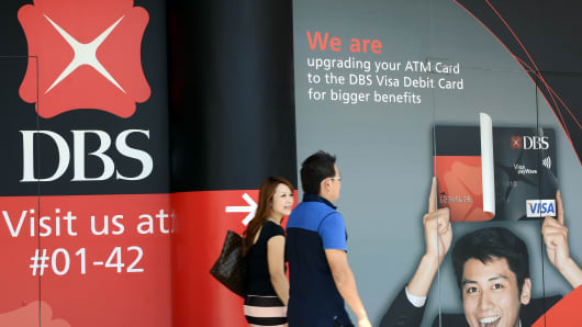 A couple walks past an advertisement outside a DBS Group Holdings Ltd. bank branch in Singapore.