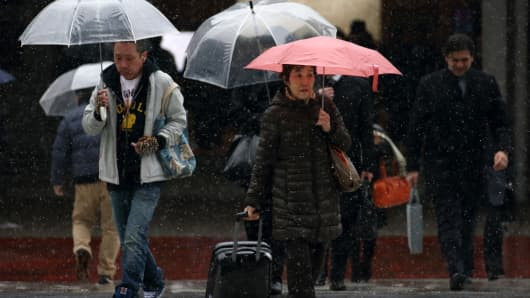 Pedestrians cross a road while carrying umbrellas as snow falls in Tokyo, Japan.