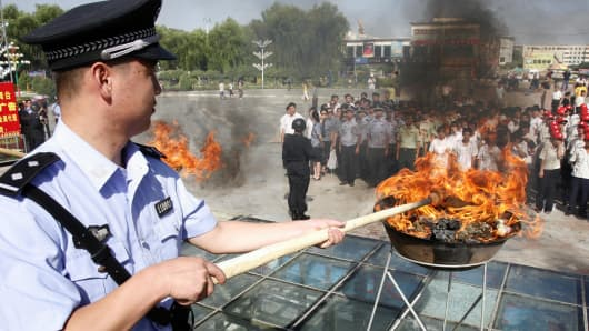 A Chinese policeman lits a cauldron filled with illicit drugs during a ceremony to mark the UN's International Day Against Drug Abuse and Illicit Trafficking, in Hami, farwest China's Xinjiang region.