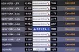A board listing departing flights shows cancellations to New York and Newark airports at Miami Internationa