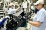Workers inspect dashboard functions on a Volkswagen AG 2012 Passat at the company's factory in Chattanooga, Tennessee.