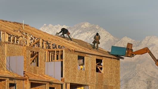 Contractors work on the roof of a new residential apartment building in Sandy, Utah.