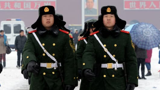 Chinese paramilitary police march at Tiananmen Square in Beijing during the first snowfall this winter.