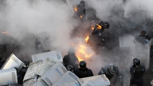 Policemen run amid flames during clashes with anti-government protesters in front of the Ukrainian Parliament in Kiev on February 18, 2014. Police on Tuesday fired rubber bullets at stone-throwing protesters as they demonstrated close to Ukraine's parliament in Kiev.