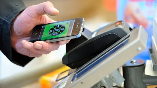A customer pays at a register with a smartphone application.
