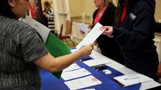 A job seeker, left, speaks to a Uline Inc. representative during a job fair hosted by JobExpo.com in Dallas, Texas.