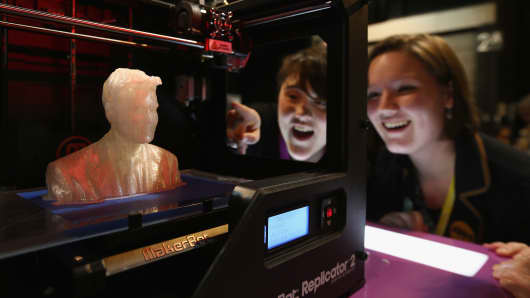 Onlookers in Glasgow, Scotland, watch a MakerBot 3-D printer produce a figure.