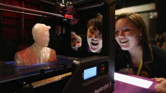 Onlookers in Glasgow, Scotland, watch a MakerBot 3-D printer produce a figure.