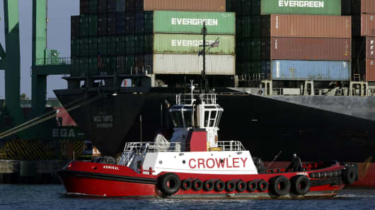 A tugboat passes a container ship in the Port of Los Angeles.
